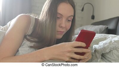femme, lit, smartphone, utilisation, maison, heureux