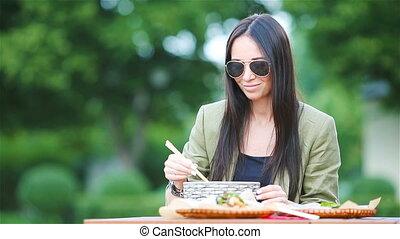 femme mange, loin, jeune, rue, prendre, nouilles