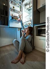 femme mange, plancher, atteindre, frigidaire, lait