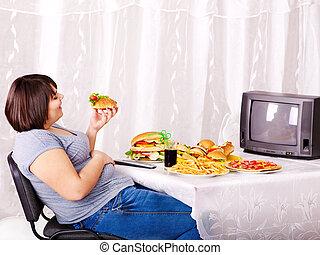 femme mange, restauration rapide, et, regarder, tv.