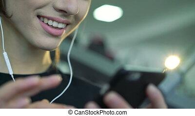 femme, mobile, gymnase, jeune, musique écouter, utilisation, téléphone., sourire