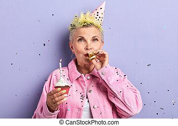 femme, noisemaker, anniversaire, célébrer, souffler, élégant, chapeau partie
