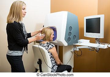 femme, optométriste, ajustement, malade, tête, quoique, regarder ordinateur, pour, retinal, vérification