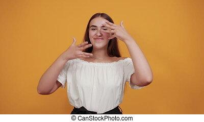 femme, ouvert, main, oeil, par, couvrant bouche, séduisant, regarder, doigts