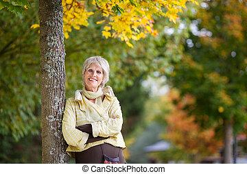 femme, parc, coffre, arbre, penchant, sourire, personne agee