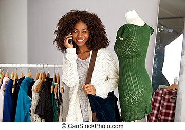 femme parler, jeune, téléphone, américain, africaine, vêtant magasin, heureux