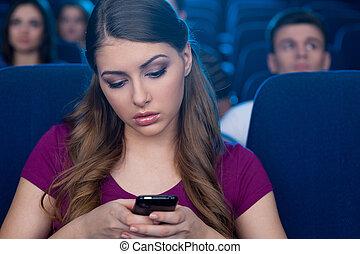 femme, percé, cinéma, mobile, film, cinema., regarder, jeune, il, regarder, téléphone, quoique, tenue, sentiment