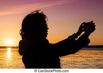 femme, plage, pendant, jeune, elle-même, sunset., selfie, image, prendre, beau