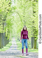 femme, porter, caoutchouc charge, marche, dans, printemps, ruelle