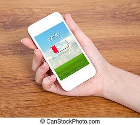 femme, possession main, a, toucher, blanc, téléphone, à, bas, batterie, sur, a, écran, contre, les, fond, de, a, table bois