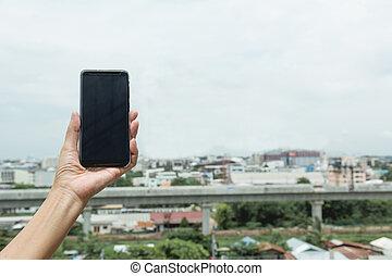 femme, possession main, intelligent, téléphone, à, bâtiments, arrière-plan.