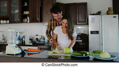 femme, préparer, sain, légumes, cuisine, ensemble, conversation, dîner, découpage, embrasser, homme, couple, cuisine