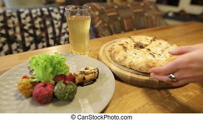 femme, prend, kubdari., meat., géorgien, mains, fou, traditionnel, khachapuri, pkhali, multi-coloré, plat, morceau