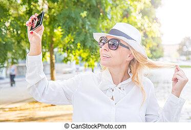 femme, prendre, jour ensoleillé, sourire, selfie