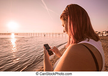 femme, regarder, téléphone portable, coucher soleil, mer, pendant