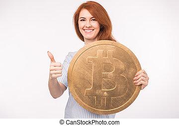 femme, roux, grand, projection, haut, bitcoin, cryptocurrency, arrière-plan., pouces, tenue, blanc, concept., investissement
