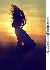 femme, sauter, à, coucher soleil