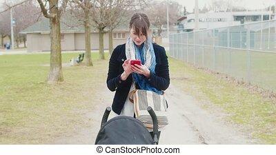 femme, sends, texte, pousser, jeune, quoique, stroller., message