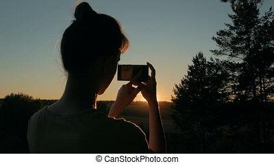 femme, silhouette, photo, prendre, parc, surprenant, smartphone, coucher soleil