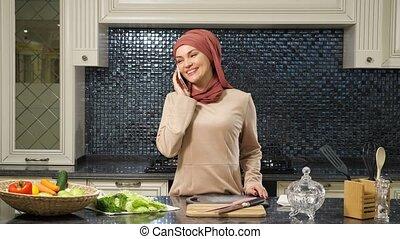 femme, smartphone, table cuisine, pourparlers, hijab, debout