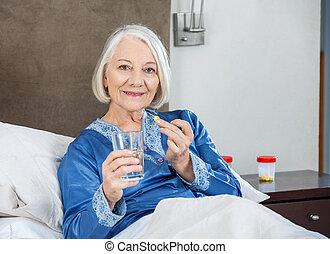 femme, soins, prenant médicament, maison, sourire, personne agee