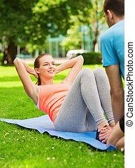 femme souriante, faire, exercices, sur, natte, dehors