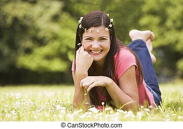 femme souriante, fleurs, mensonge, dehors