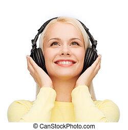 femme souriante, jeune, écouteurs