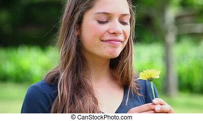 femme souriante, jeune, fleur, sentir