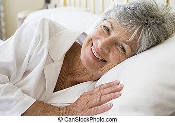 femme souriante, mensonge, lit