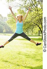 femme souriante, parc, sauter