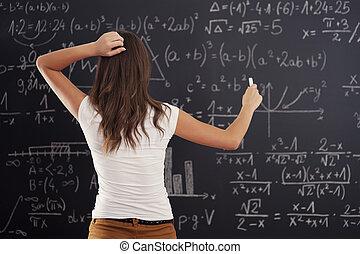 femme, tableau noir, jeune regarder, problème, math