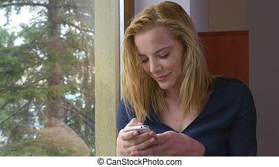 femme, texting, jeune, fenêtre, séduisant, message, heureux