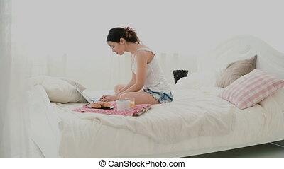femme, utilisation, séance, ordinateur portable, blanc, jeune, lit, chatting., petit déjeuner, brunette, pc, dactylographie, pendant, girl, home., message