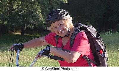 femme, vélo, regarder, appareil photo, sourire, personne agee