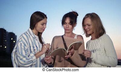femmes, discuter, magazine, it., debout, dehors, regarder