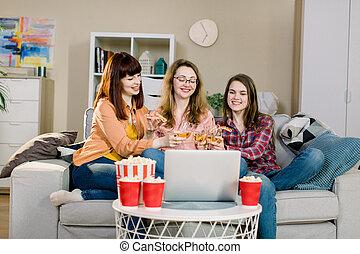 femmes, manger, film regardant, jeune, trois, rire, savoureux, pop-corn, maison, boire, ordinateur portable, vin