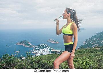 femmina, atleta, acqua potabile, ascoltando musica, in, auricolari, riposare, e, recuperare, da, correndo, o, esercitarsi, standing, cima, il, montagna, contro, mare, isole, cielo nuvoloso, in, fondo