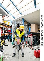 femmina, lavoratore, con, martello pneumatico, in, uno, warehouse.