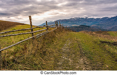 fence along dirt road in mountainous rural area....