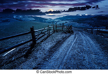 fence along the country road at night - fence along the...
