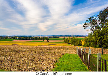 Fence and view of farm fields in rural Lancaster County, Pennsylvania.