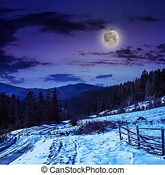 fence by the road to snowy forest in the mountains