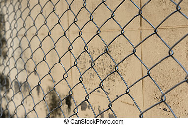 Fence from steel mesh on grunge cement wall backgroud