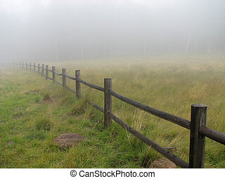 fence in fog - a wooden fence fades into the fog with a...