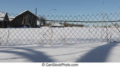 fence mesh in the village in winter. smooth motion from right to left