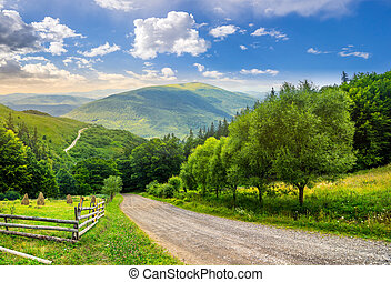 fence near road down the hill with forest in mountains at...
