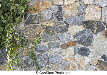 Fence of ornamental stone, ray background stylized in a natural wild stone with green branches