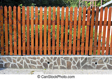 fence of wooden slats on the stones.