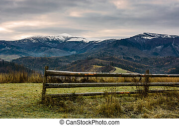 fence on grassy meadow in autumn. landscape of mountain...